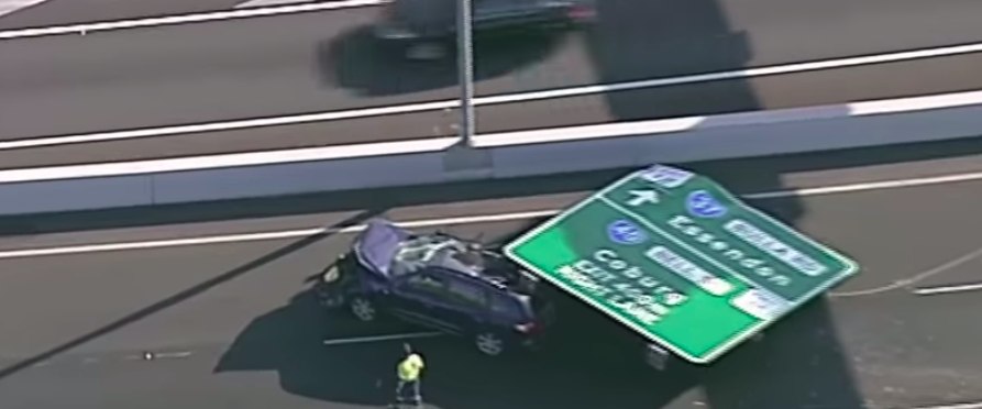 Watch dashcam video of driving car crushed by highway sign