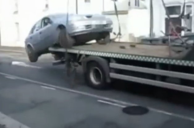 Watch as Upset Motorist Drives Off Flatbed Truck to Avoid Parking Ticket