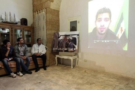 A former colleague of U.S. aid worker Abdul-Rahman Kassig, is seen on a projection screen ...