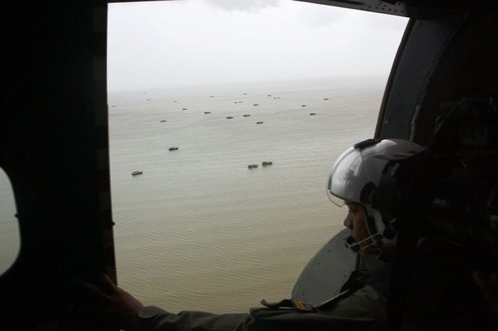 An Indonesian navy crew member searched for parts of AirAsia Flight 8501 above the Karimata Strait.