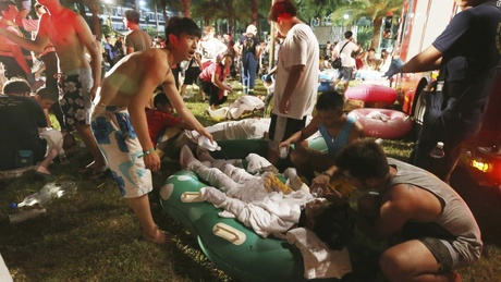 Emergency rescue workers and concert spectators tend to injured victims from an explosion during
