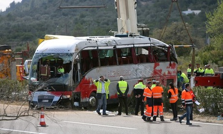 Rescue workers remove the coach after a crash on the AP-7 motorway in the province of Tarragona