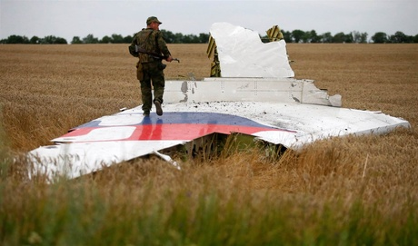 An armed pro-Russian separatist stands on part of the wreckage of MH17