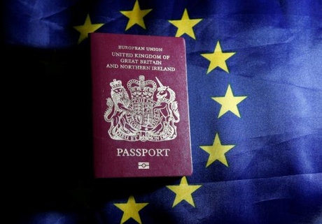 A British passport is pictured in front of an European Union flag