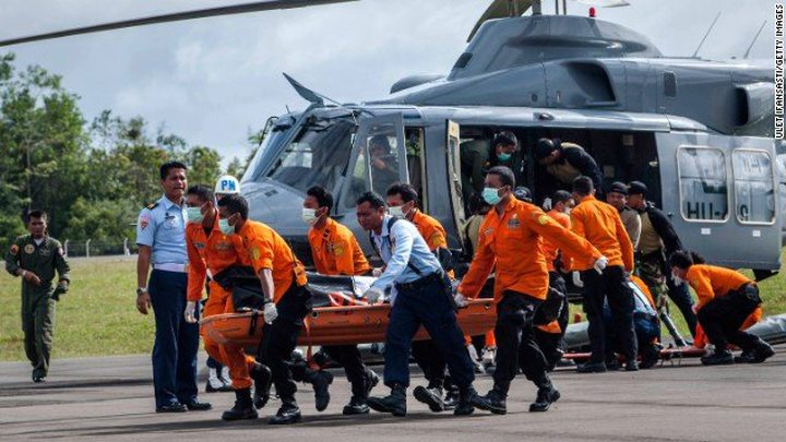 Members of a search and rescue team carry the body of a victim of AirAsia Flight QZ8501 at Iskandar