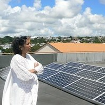 Andrea Gungadin on the roof with her solar panels