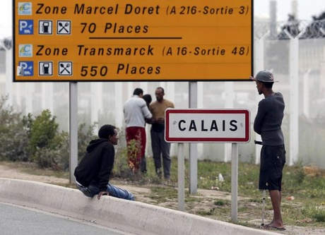 Migrants stand near a city sign along a road near the makeshift camp called ''The New Jungle''