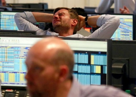 A trader from BGC, a global brokerage company in London's Canary Wharf financial centre reacts...