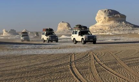 Four-wheel drive cars cross the sand dunes in the Egyptian western desert and the Bahariya Oasis