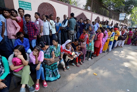 People waited to deposit their old high-denomination currency notes on Saturday outside a bank